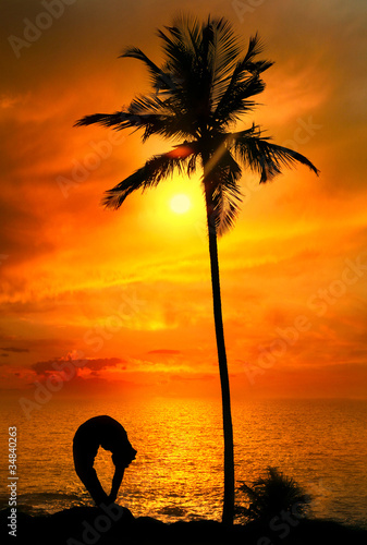 Yoga silhouette tiriang mukhottanasana pose at sunset