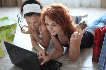 Two pretty girls shopping over internet
