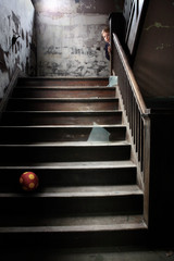 Stairwell littered with broken glass a ball and a child