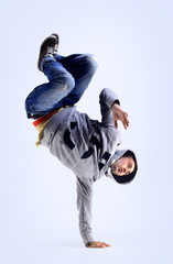 Young handsome fresh man breakdancing with