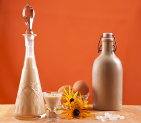 glass of eggnog with carafe on orange background
