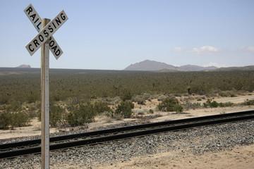Bahngleise in der Wüste mit Schild Railroad crossing
