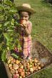 Jeune fille debout dans une brouette mangeant une pomme