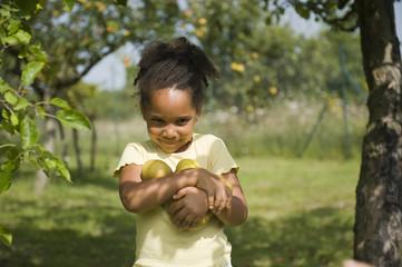 Jeune fille portant des pommes dans ses bras
