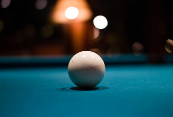 A single white billard ball against a billard table