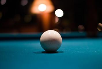 A single white billard ball against a billard table