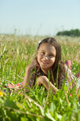 teen girl lying in meadow grass