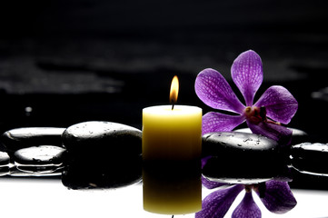 burning spa candles with pink orchid reflection