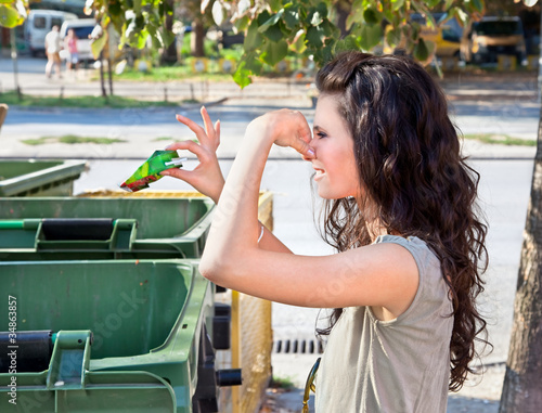 Woman throws garbage in dumpster