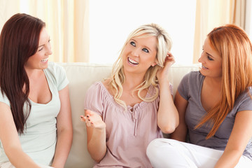 Joyful friends sitting on a sofa