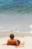 Ragazzo che prende il sole in riva al mare
