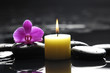 spa scene -aromatherapy candle and pink orchid on zen stones