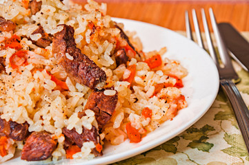 Pilaf made of rice, fresh carrots and meat.