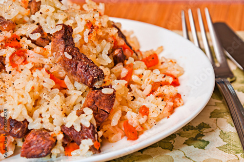 Pilaf made ​​of rice, fresh carrots and meat.