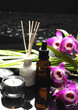 massage oil and candle with orchid and green leaf