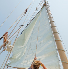 Crew member raising sail on the private sail yacht.
