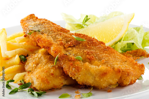 Fotobehang Restaurant Fish dish - fried fish fillet, French fries with vegetables