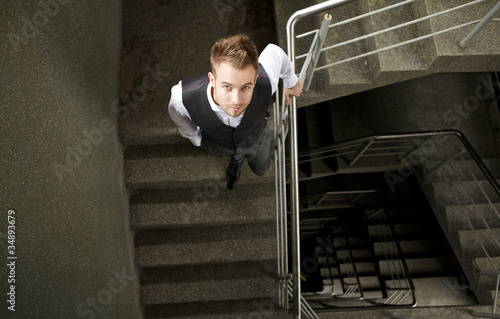 Young attractive man pose on ladder.