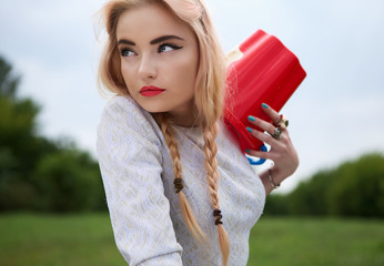 Fashionable young blonde with red bucket