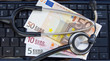 Stethoscope and euro banknotes on laptop's keyboard
