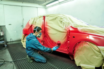 Painting a red car.