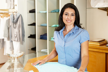 Hispanic woman working in fashion store