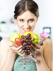 beautiful girl holds fruits in the kitchen