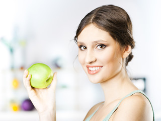 woman with green apple in kitchen