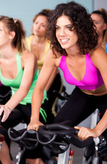 Group of four people spinning in fitness club