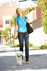 Woman walking with dog in city street