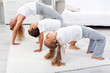 Woman and kids doing gymnastic exercises at home