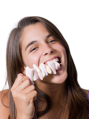 Pretty young woman eating marshmallows on a stick