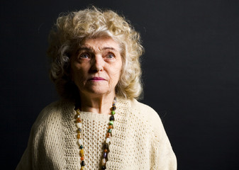 portrait of woman in her eighties on black background