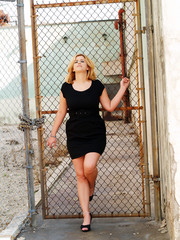 Young plump caucasian woman black dress cyclone fence
