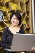 asian woman using laptop working smiling.
