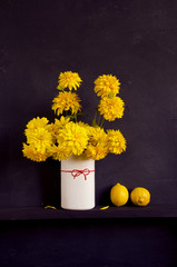 still-life with yellow dahlia and lemons