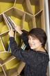 arranging book, a woman arranging books on bookshelf.