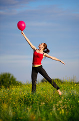 Woman jumping with a red balloon