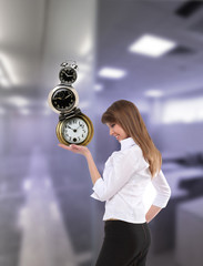 businesswoman in office holding clock pyramid