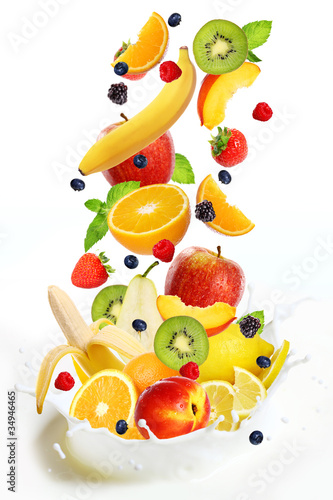 Lot of different fruits falling into milk