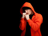furious young man in orange sweatshirt, black background