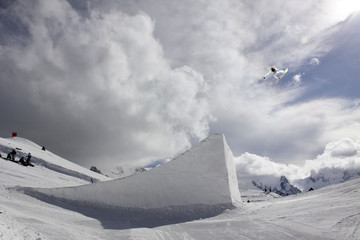 snowboarder taking big air jump with cloudy sky