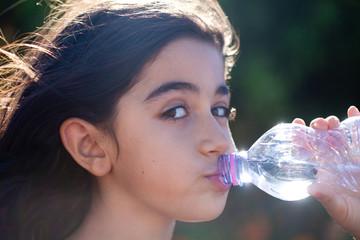 bambina beve acqua dalla bottiglia
