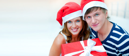 Portrait of young pretty couple standing indoors wearing Santa C