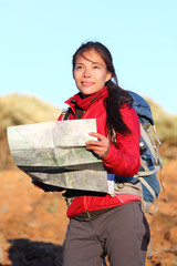 Hiking woman in nature holding map