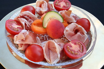 Appetizer with Serrano ham, apricot and tomato