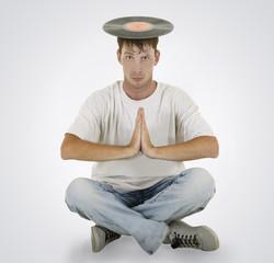 DJ sitting on the floor with vinyl on his head