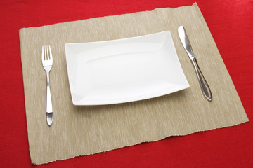 white plate fork and knife on red table