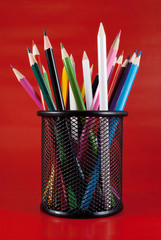 Colored pencils in a black mesh holder.