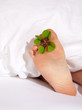 Happy feet of a child under a white blanket with shamrock